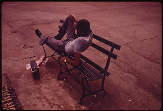Man Lounging on a Park Bench with His Radio on the Reis Park Boardwalk in New York City ... 07/1974 | by The U.S. National Archives