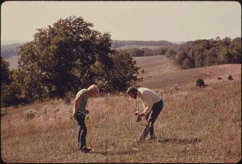 Ken Babcock, Right, a Native of Doniphan County Kansas, and a Youth Examine Some of the Plants in an Overgrazed Prairie Area Bordered by Forest...09/1974 | by The U.S. National Archives