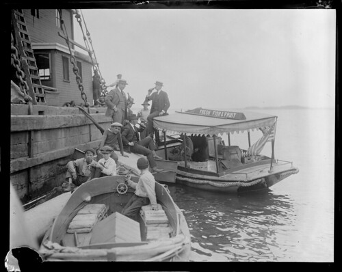 "Boat with sign ""Fresh Fish and Fruit"" delivers bottled drinks to men on pier (possibly Prohibition selling illegal alcohol) 