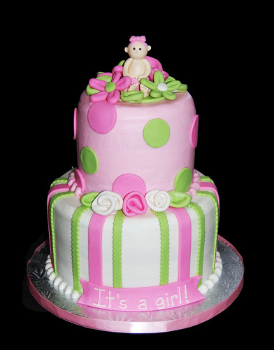 pink and green baby shower cake topped with a baby in a flower patch | by Sweet Shoppe Mom and Simply Sweets