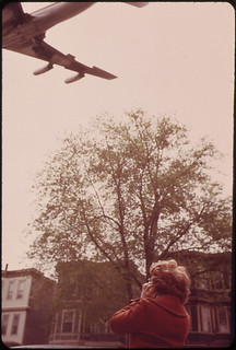 Mary Bruno Holds Her Ears Against Noise of Jet Coming in for a Landing on Runway 15r at Logan Airport | by The U.S. National Archives