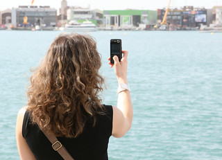 Tourist on holiday using mobile cell phone | by Moomettes