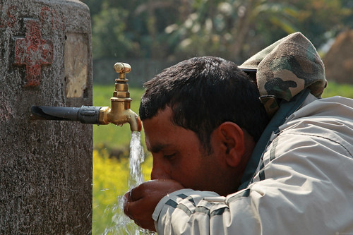 Man drinking from water tap in Kaski, Nepal | by World Bank Photo Collection
