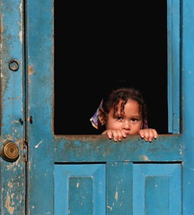Young Cuban girl looking out her front door | by **El-Len**