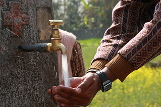 A villager of Kaski shows how their water tap works | by World Bank Photo Collection