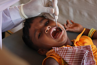 A dentist examines a young child's teeth | by World Bank Photo Collection
