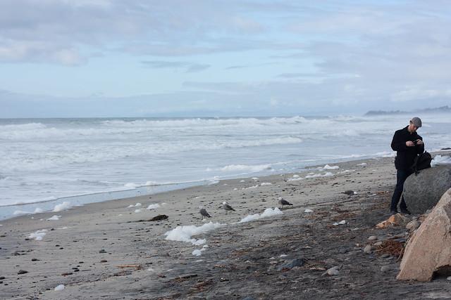 The tide exhales foam