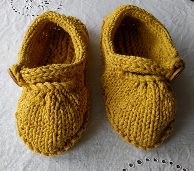 An image of two yellow handknitted slippers on a white linen.