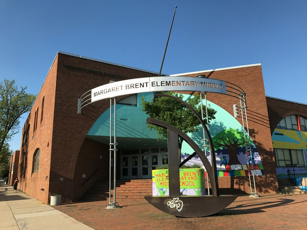 The corner of a brick school building with a metal sign and metal modernist sculpture in the foreground.
