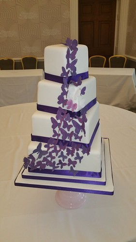 Cascade of purple butterflies offset square four tiered wedding cake. | by platypus1974