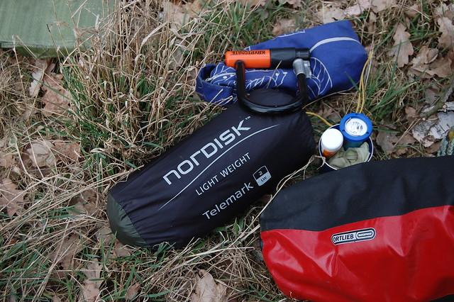 Bild: ein wasserdichter Ortlieb Packbeutel, ein verpacktes Nordisk Telemark 2 LW Zelt.