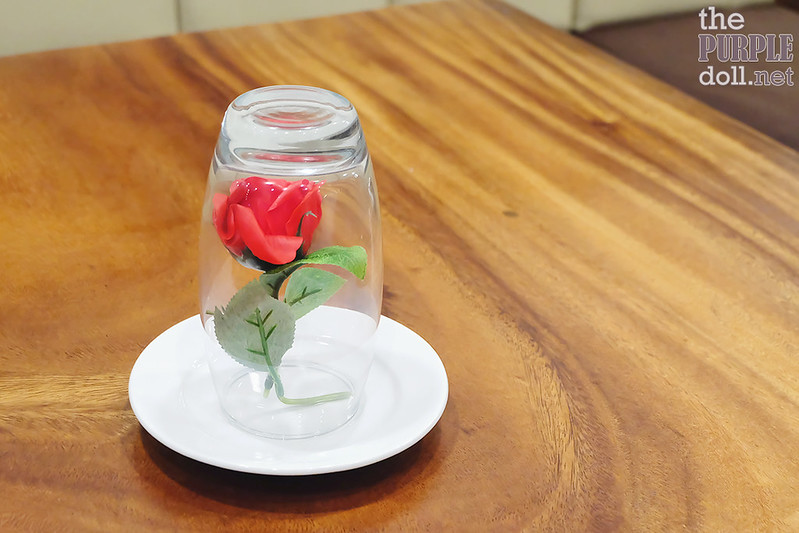 Glassed flower centerpiece reminds of Beauty and the Beast