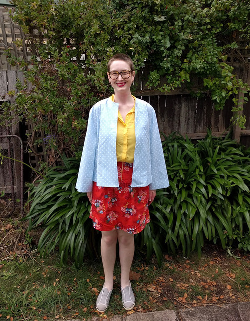 A woman stands against a garden fence. She wears a blue and white polka dot sun jacket, yellow shirt, and red floral print skirt.