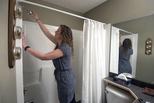 Homeowner Rihanna McPhee checks the pressure of her new shower head