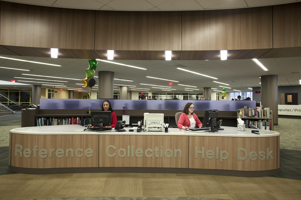 Reference collection help desk in the library with two librarians in front of the computers