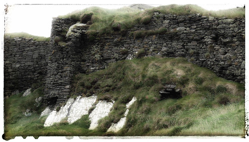 Stone wall of castle ruins at Galley Head in Ireland painted in the photo app Snapseed