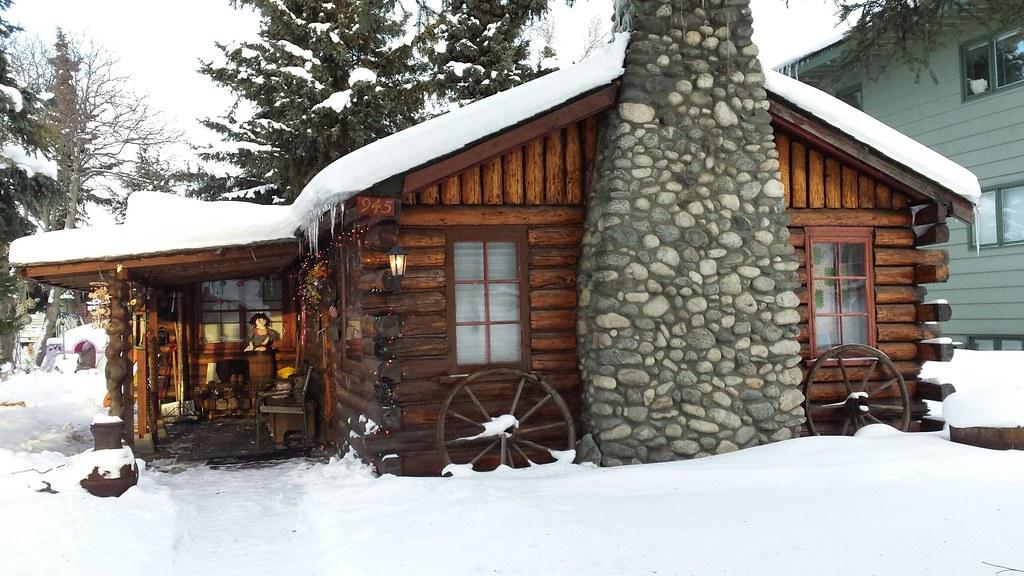 daytime winter log cabin doll on porch wagon wheels roc flickr