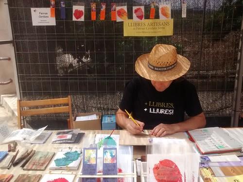 Escriptor artesà amb obra assecant-se al fons
