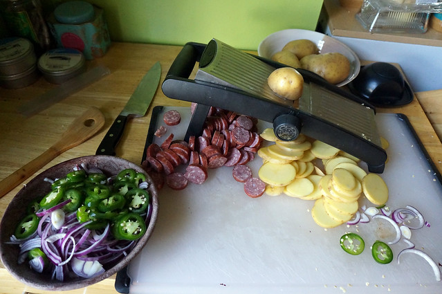 A process shot: a mandoline slicer surrounded by heaps of sliced potato, sausage, onion, and jalapeño.