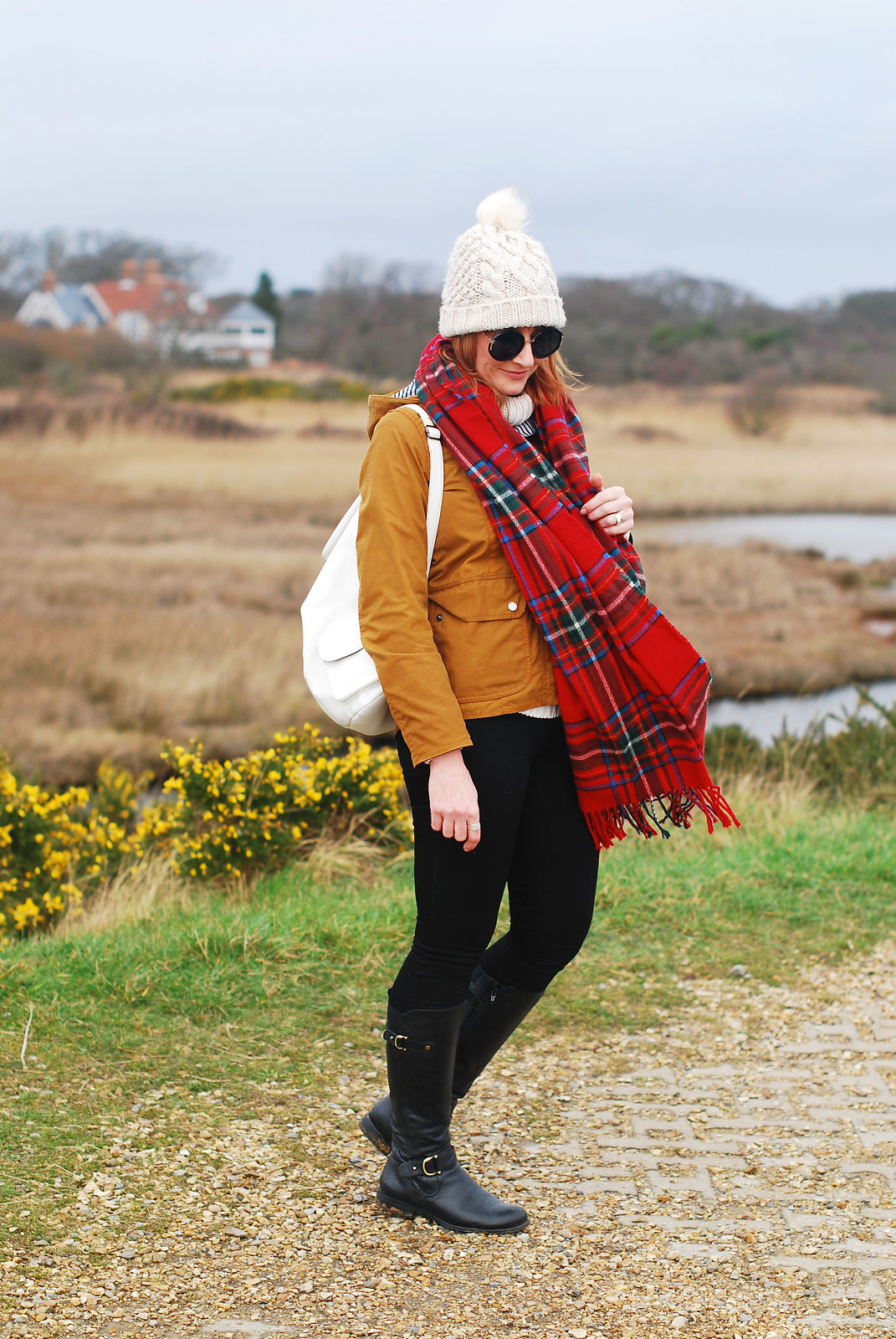 Cold weather preppy outfit for the coast: Brown Barbour jacket cream bobble hat and roll neck red tartan scarf black skinnies and riding boots | Not Dressed As Lamb, over 40 style blog