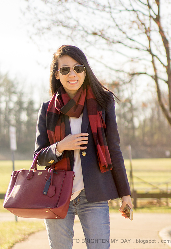 red buffalo check scarf, navy blazer, light pink sweater, burgundy tote with navy anchor luggage tag, lightwash jeans