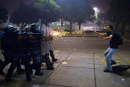 Cristophe Simon (AFP/Gettyimages). Remembering 2013: A demonstrator is shot by rubber bullets as riot police charge after clashes erupted during a protest against corruption and price hikes in Rio de Janeiro, Brazil. | by Jordi Bernabeu