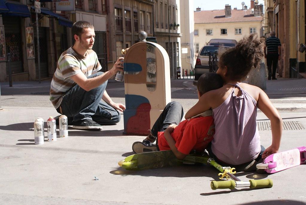 Street art : Graffeur en pleine création devant des enfants dans les Pentes de la Croix Rousse à Lyon.