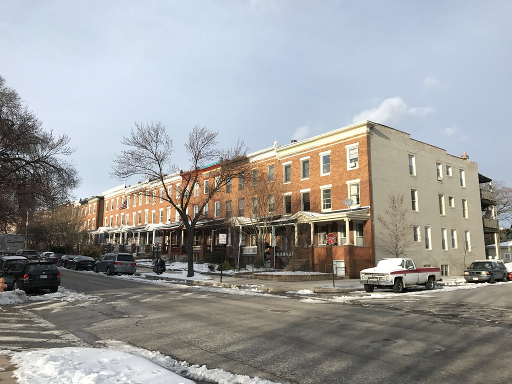 A block of brick rowhouses with porches.
