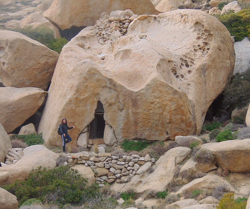 Posing to demonstrate size and proportions of a stone house. In general this is a place as if from neolithic times. Several hollow rocks in this area have served as human shelters through the ages.