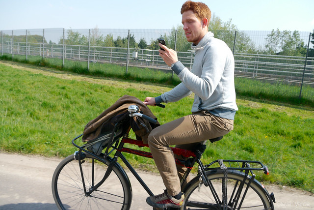 Daniel checking something on his phone while bicycling to Delft from Rotterdam