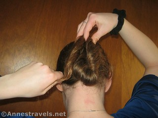 Creating the vertical oval while making a Hair Elastic Twist Up - 12 Pretty & Practical Hiking Hairstyles
