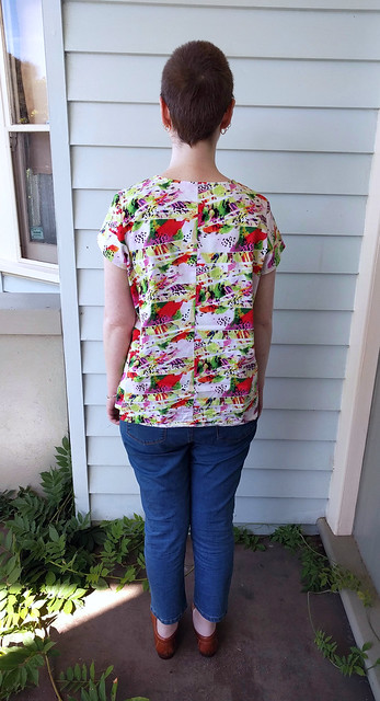 A woman stands in front of a weatherboard wall. She wears a colourful printed t-shirt, crop jeans, and leather loafers.