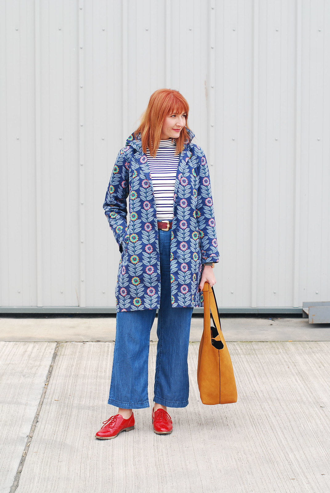 Bright spring weather outfit: Floral Seasalt raincoat  high neck stripe Breton top  wide leg cotton denim trousers  red brogues  ochre bucket bag | Not Dressed As Lamb, over 40 style