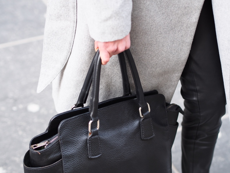 grey coat and black leather handbag
