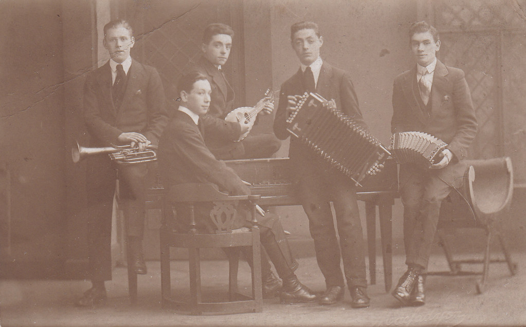 Early twentieth century photograph of five very young men, pictured with piano, some kind of small horn, a mandolin, a two-row button accordion, and an anglo-concertina.