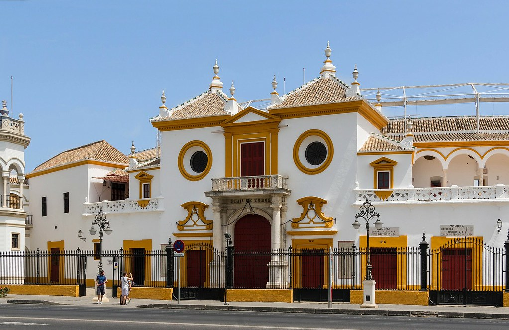 The outside of the Seville Bullring. Against the blue sky the white building has a red and yellow trim. The arches and round windowns make it look very interesting from the outside.