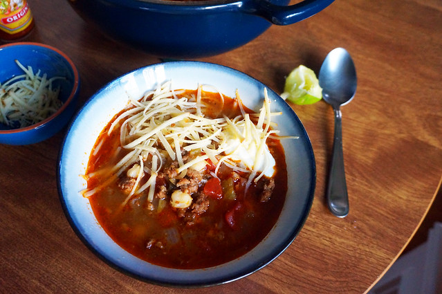 A bowl of quick and lazy pozole, dressed with a little cheese and sour cream. A squeezed lime wedge, bright green, rests near the spoon on the table in the background
