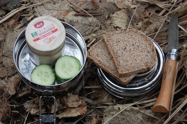 Bild: Mittagspause. Ein Behälter für Essen aus Metall, Vollkornbrot, Aufstrich und Gurkenscheiben sind da und mein Opinel Taschenmesser