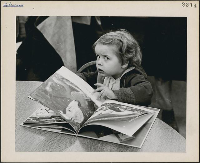 Three-year-old Jennifer Adair with a book, Montreal, Quebec / Une lectrice de trois ans, Jennifer Adair, lit dans une bibliothèque publique de Montréal (Québec)