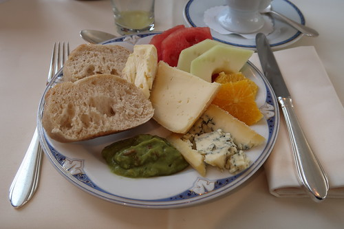 Diverse Bio-Käse und Avocadocreme zu Baguettescheiben sowie frisches Obst