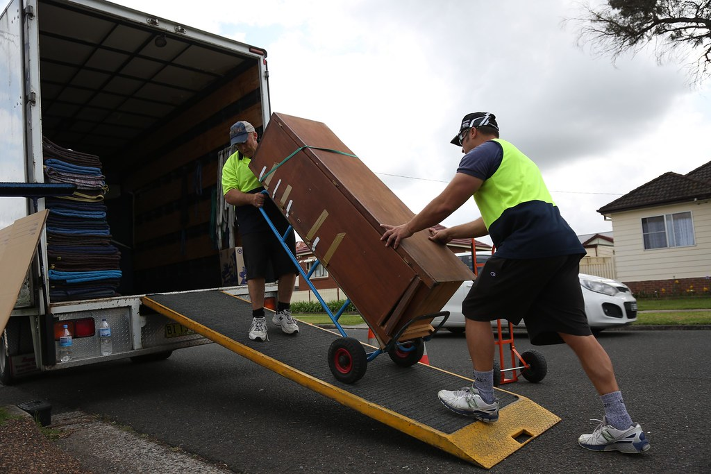 Men moving packing items into a truck