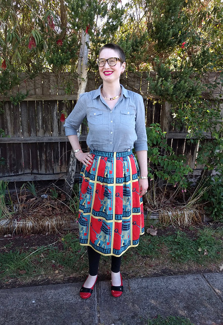 A woman stands in front of a garden fence. She wears denim button up shirt, Dalek-print skirt, and black and red polka dot flats.