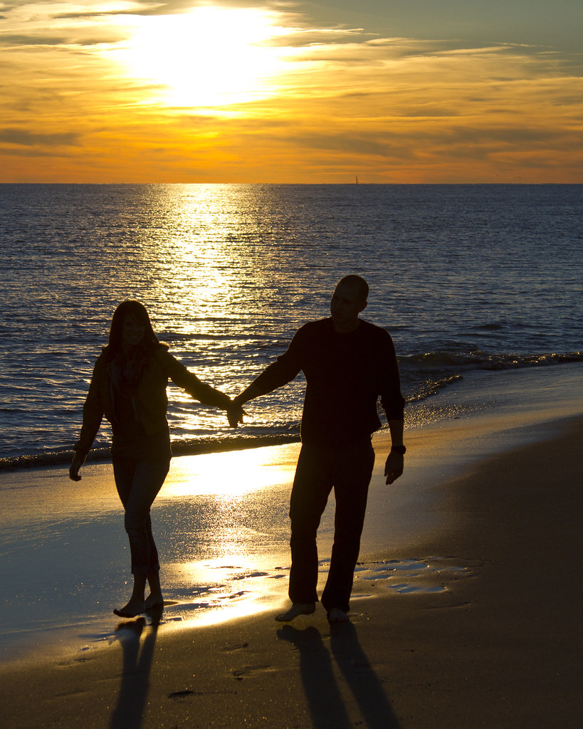 People Walking On The Beach Holding Hands