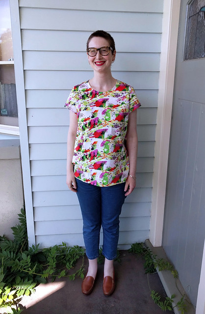 An image of a young woman, standing in a veranda in front of a weatherboard wall. She wears large glasses, a t-shirt with a colourful print reminiscent of shattered glass, crop jeans, and leather loafers. She is smiling.