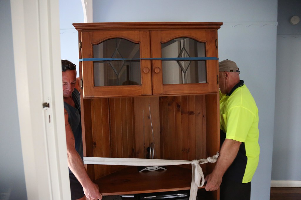Professional Movers moving a cabinet