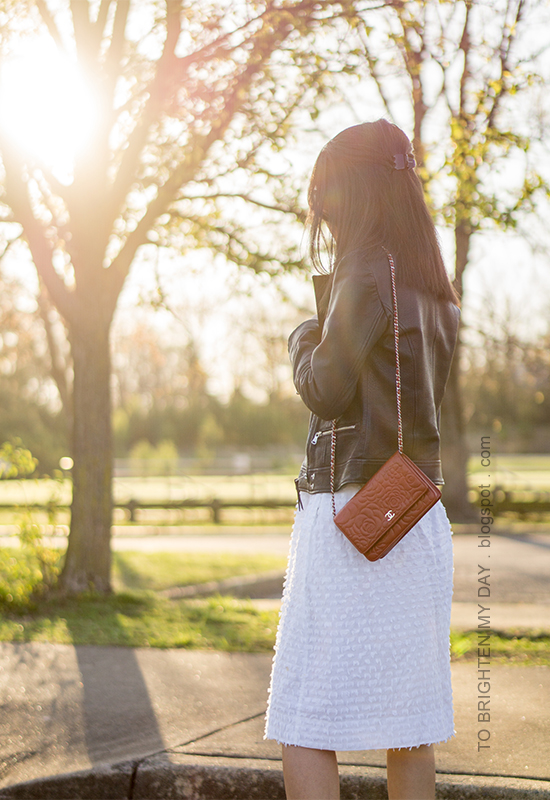 black leather jacket, red shoulder bag, white clip dot midi skirt