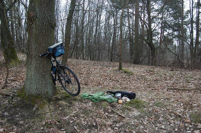 Bild: Das Fahrrad lehnt an einem Baum, auf dem Waldboden liegt eine Regenjacke, der Proviantbeutel und Frühstückskram