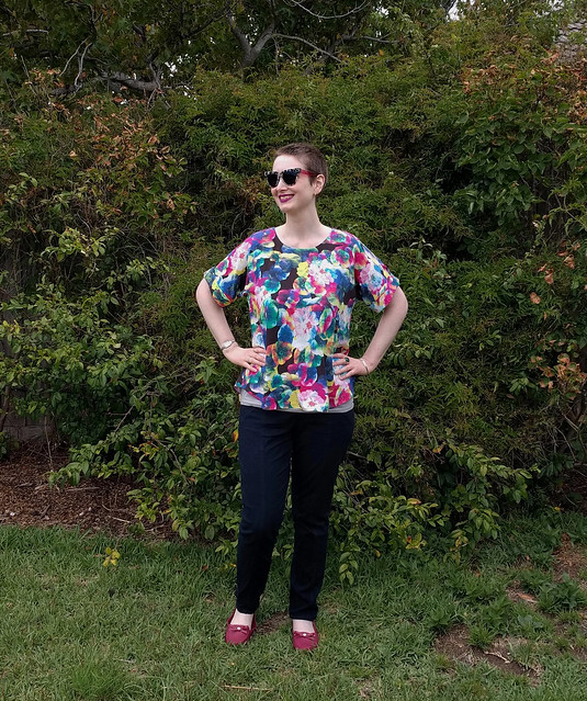 A woman stands in a garden, wearing a black kimono sleeve top with colourful gem floral pattern, black pants and red shoes.