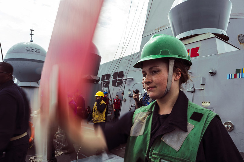 Sailor signals from USS Green Bay to USNS Richard E. Byrd during a replenishment-at-sea.