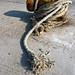 Thick rope tied around small  metallic  pillar